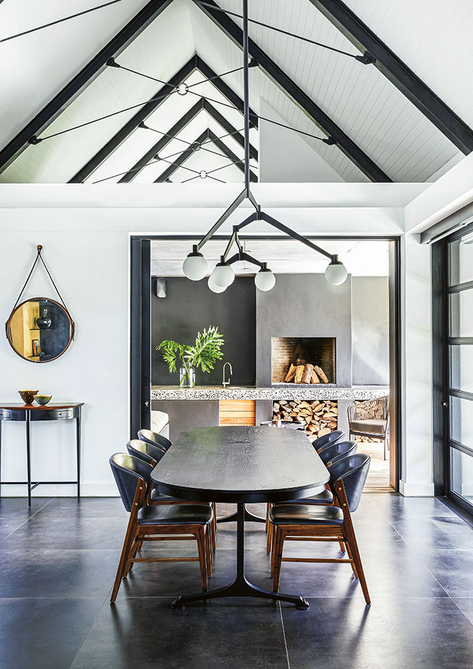 The pitched roof allows the articulated chandelier – 'Constellation' by Julian McGowan and Bronze Age Studio – to make a hanging statement over the custom Gregor Jenkin table. Leather and kiaat chairs complete the scene.