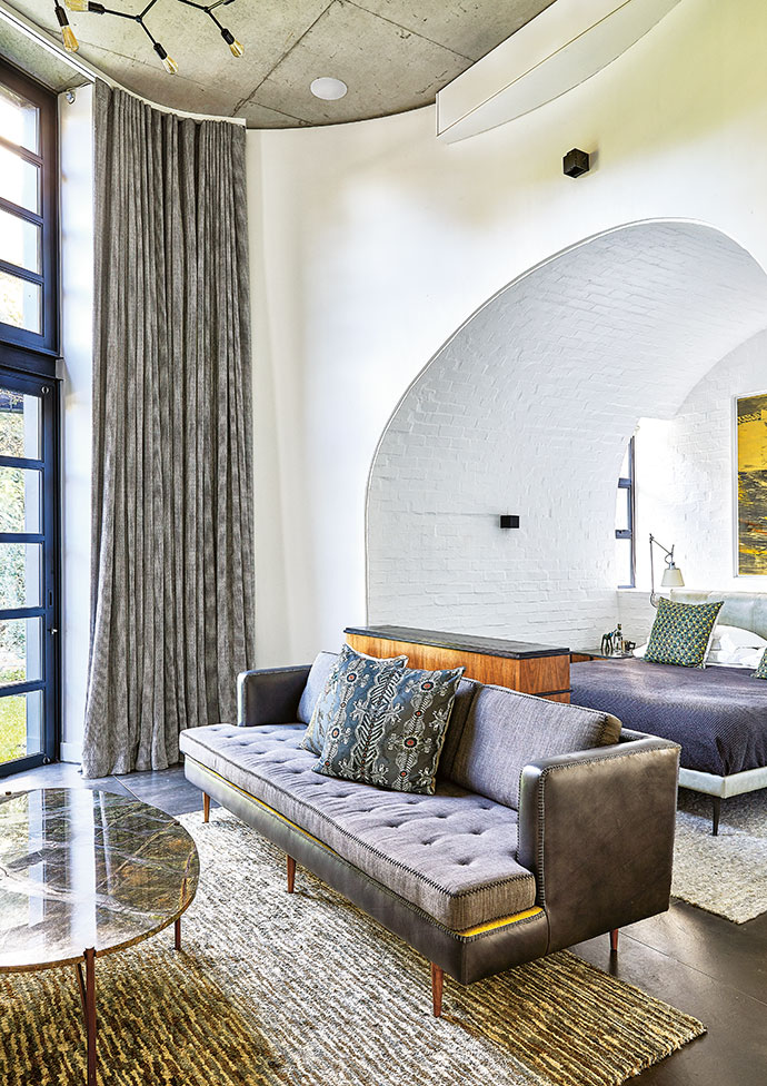 The master bedroom fits into the silo of the home – an architectural element complementing the barn-like design. It has its own cosy lounge area, furnished with a Casamento sofa and GUILD coffee table.