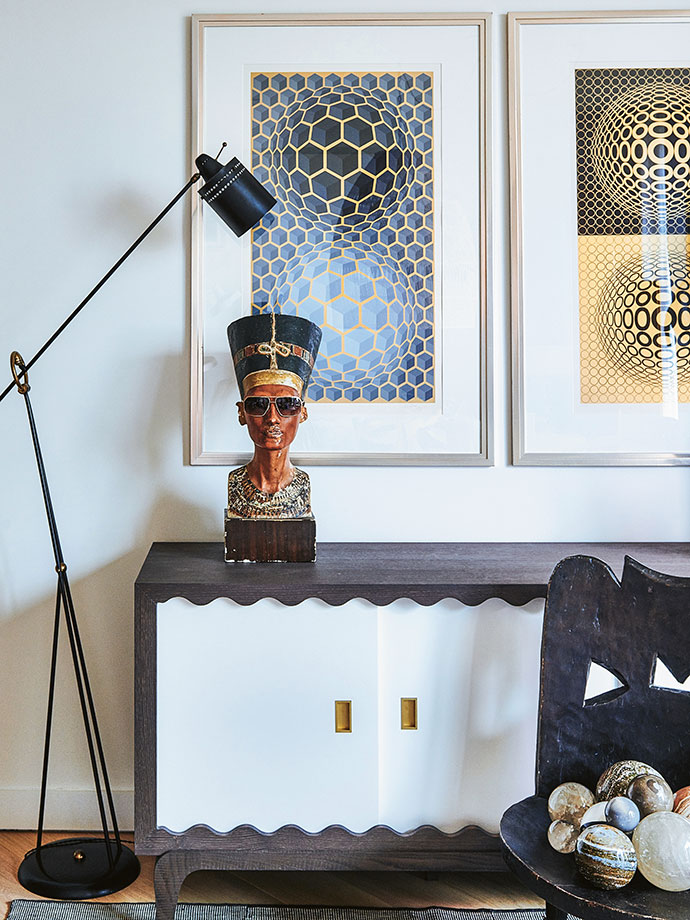 A vintage Museum model of Nefertiti (circa 1920) sits atop a custom-designed HZI cabinet in the living room, with a vintage floor lamp by Pierre Guariche. The paintings on the wall are by Victor Vasarely, while the stool in the foreground is by the Jimma Tribe of Ethiopia.