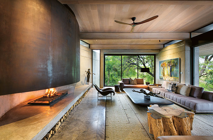 "The curve of the fireplace at Mapogo House softens the otherwise harsh, graphic lines of the formal lounge. Gail Catlin's cheetah sculpture and a painting from her ""Happy Tree"" series are complemented by Angus Taylor's bronze and aluminium piece, Grounded."