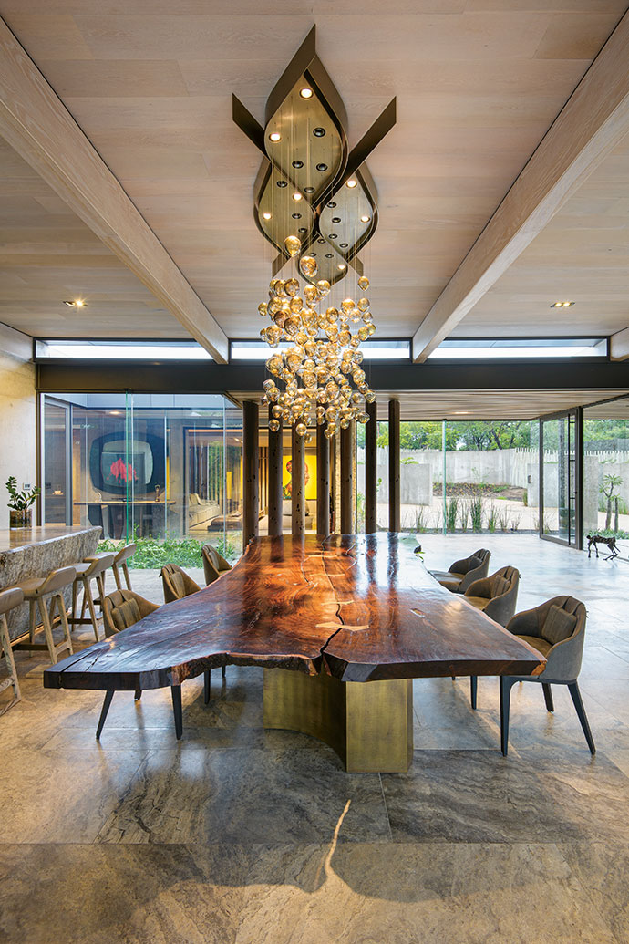 Keeping to theme, a Martin Doller chandelier hangs above the solid Pierre Cronje table in the Mvula House indoor dining room.
