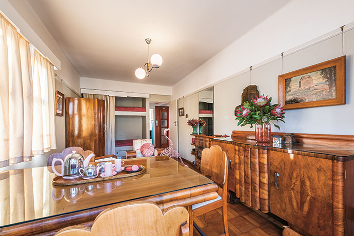 The beautifully restored interior of one of the Holyrood apartments Robert owns features parquet flooring, an original bookshelf/mantelpiece and light fixture, and Art Deco armchairs he picked up at Milnerton Market.