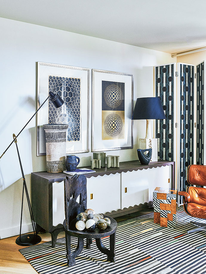 On the HZI cabinet in the living room is a display of vintage art studio pottery and a collection of Alvar Aalto forms. The floor lamp is a vintage Pierre Guariche piece, and the paintings on the wall are by Victor Vasarely.