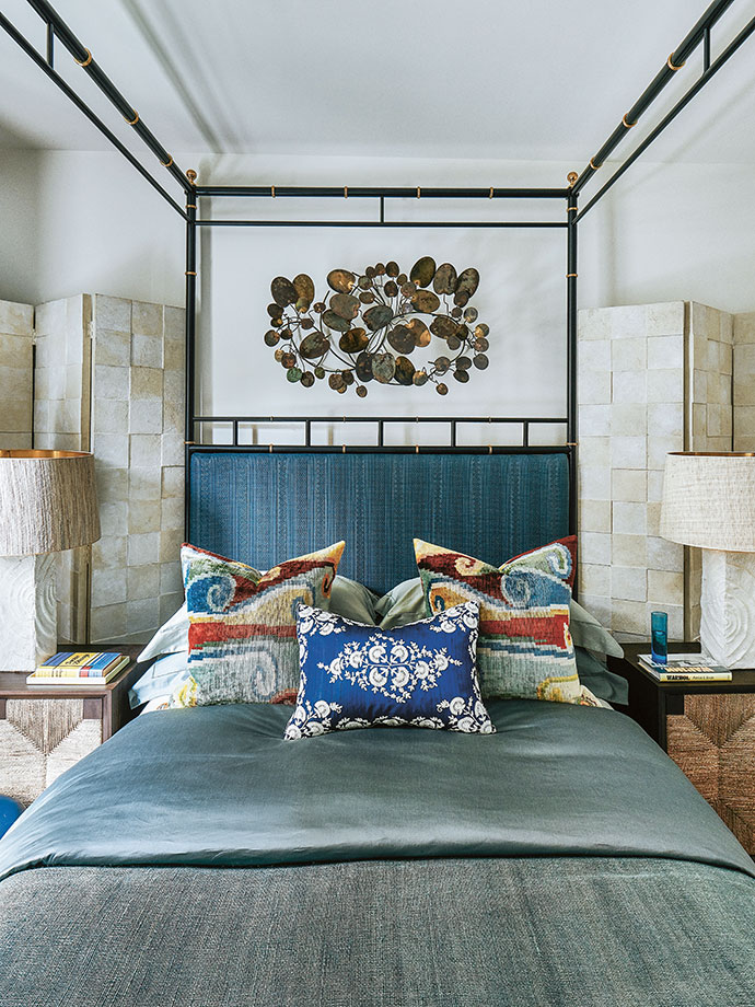 The metal wall sculpture above the bed is by Curtis Jeré, while the colourful silk Ikat cushions are from Istanbul.