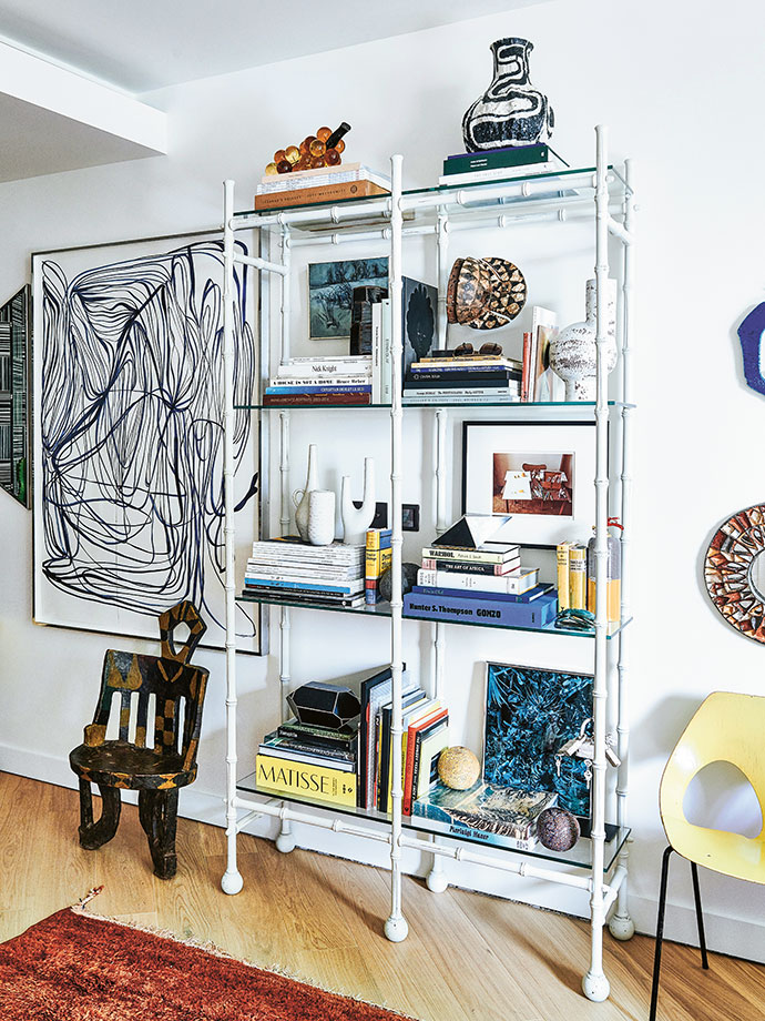 A faux-bamboo shelving system by HZI is filled with an assortment of things that Hubert holds dear. On the top right shelf is a ceramic vessel by Johannes Nagel, while a David Hockney photograph takes prides of place on the middle shelf.