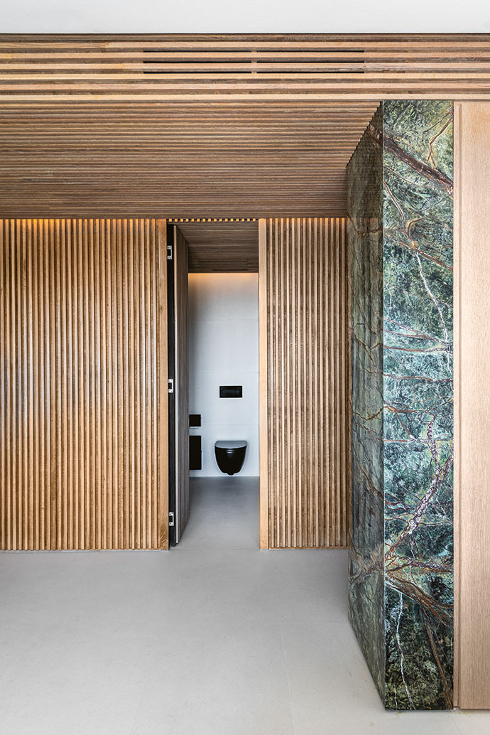 Stylish and functional, the slatted walls conceal a guest lavatory.