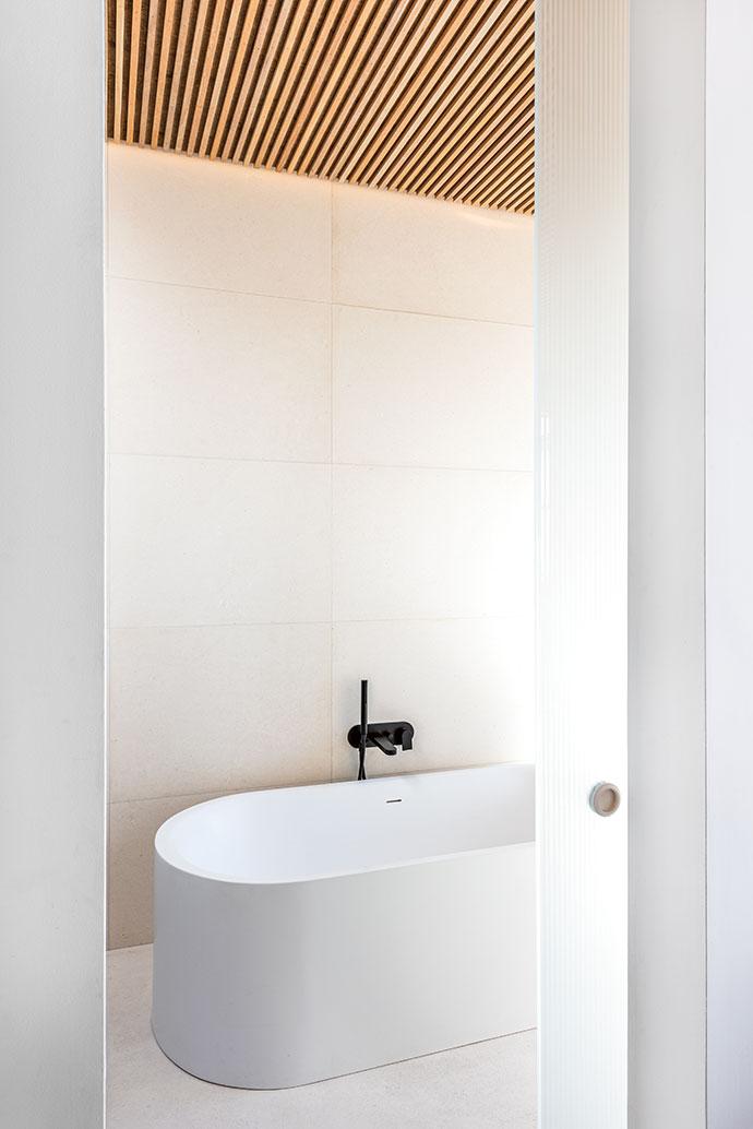 A luxurious oval soaking tub maintains the minimalist theme.
