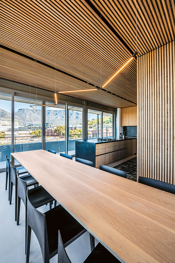 Matte-black surfaces, furniture and accessories are offset by the light wooden slats and modern light fixtures.