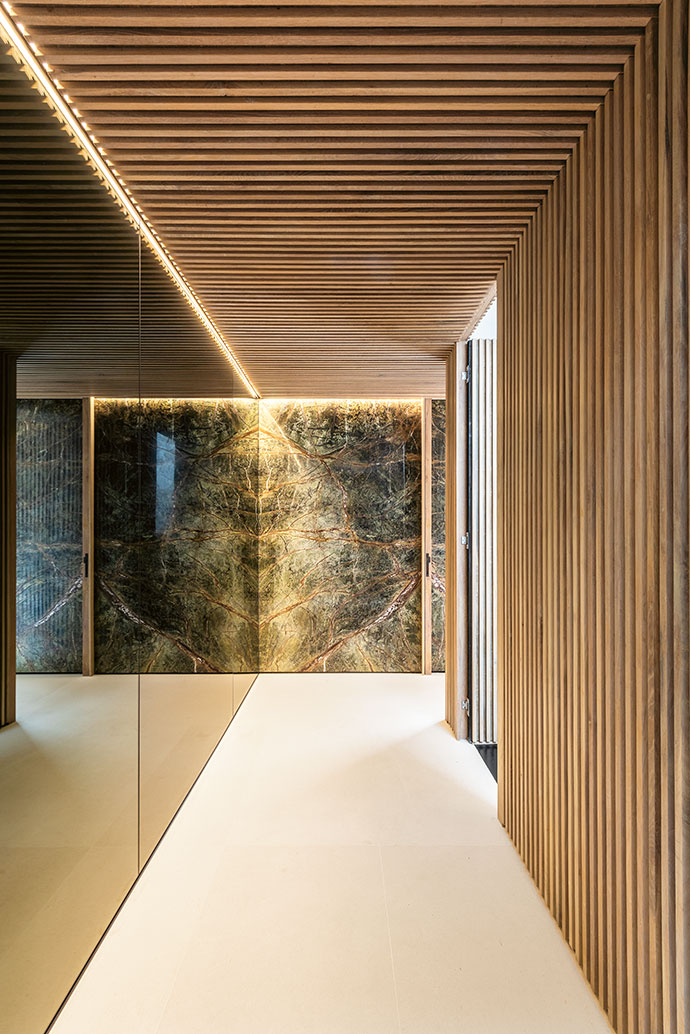 In the foyer, a subtly moody atmosphere is created by a marble-clad wall and floor-to-ceiling mirrors, which contrast with the slatted-wood ceiling and wall near the stairwell.