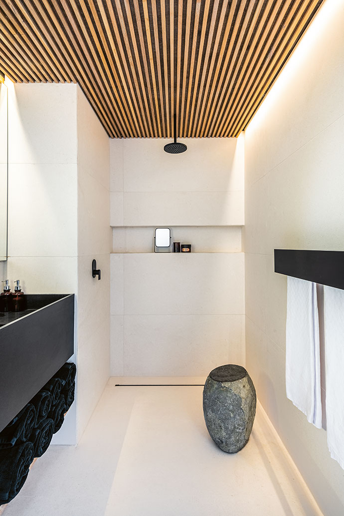 The guest bathroom combines all the elements present in the rest of the home, from wood to marble.