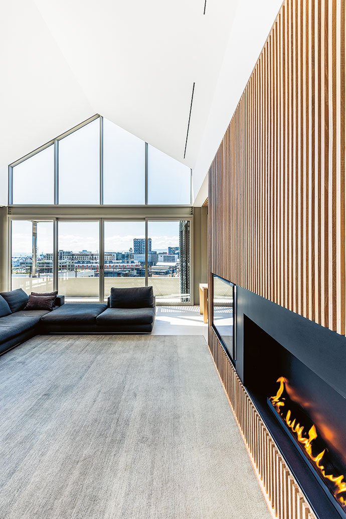 At the heart of the home is a light-filled living room with a contemporary fireplace and TV embedded in the slatted wall.