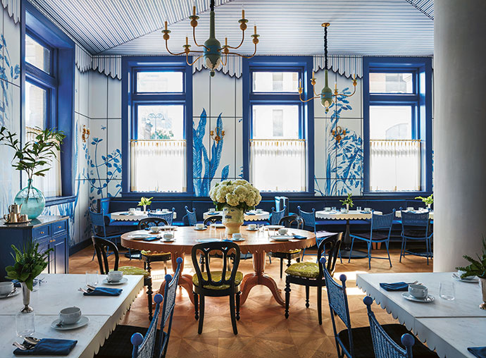 Airy and whimsical in mood, the breakfast room is a celebration of the city's great outdoors. Treated in a monochrome palette of Delft blue, the wicker chairs, tent-like ceiling and trompe l'oeil botanicals call to mind Southern garden parties.