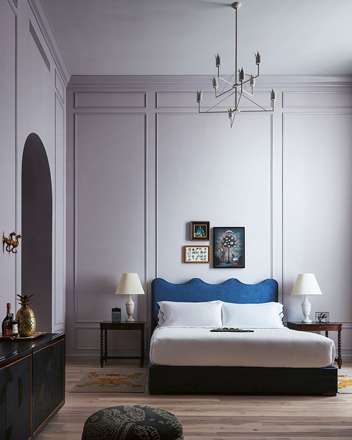 Doorframes were replaced with archways that, along with curved headboards and lavender paint, add femininity to the suites. Allegorical paintings by Louisiana artist Rebecca Rebouché hang above the beds, and boxed sculptures by Los Angeles artist Clare Crespo decorate bedside tables.