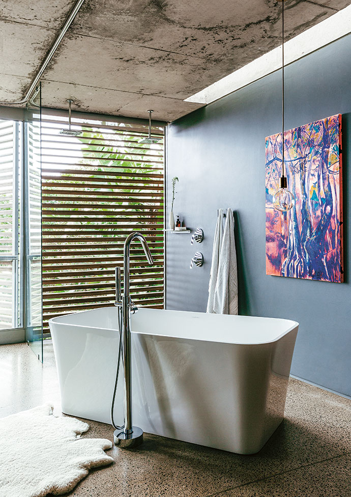 The dark walls in the main bedroom and bathroom create a cosy atmosphere, and ensure the room recedes from view from the outside, as it essentially has no front wall, just glass doors. The standalone bath is from Victoria + Albert and the standing mixer tap is by Isca. The basins, also from Victoria + Albert, sit atop a kiaat timber vanity designed by Lisa. The artwork is also one of Lisa's.