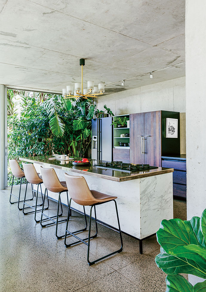 The galley-style kitchen is an entertainer's dream, with @home bar stools reupholstered in vinyl and a Marc Newson-designed hob from Smeg.