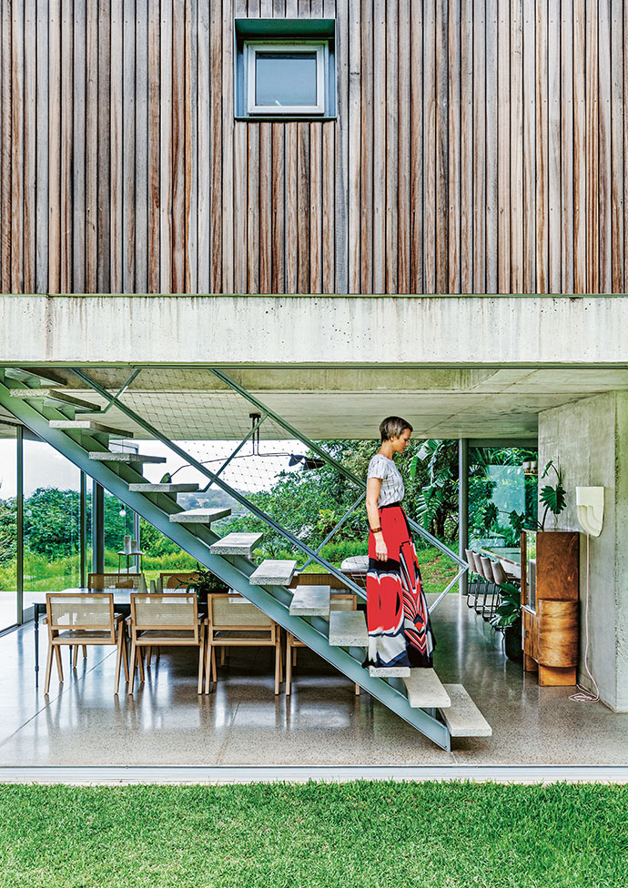 Owner Lisa Twyman on the staircase – which has a steel frame and polished concrete treads – that leads to the first-floor bedrooms of her home. The flooring is made of polished concrete with crusher dust aggregate.