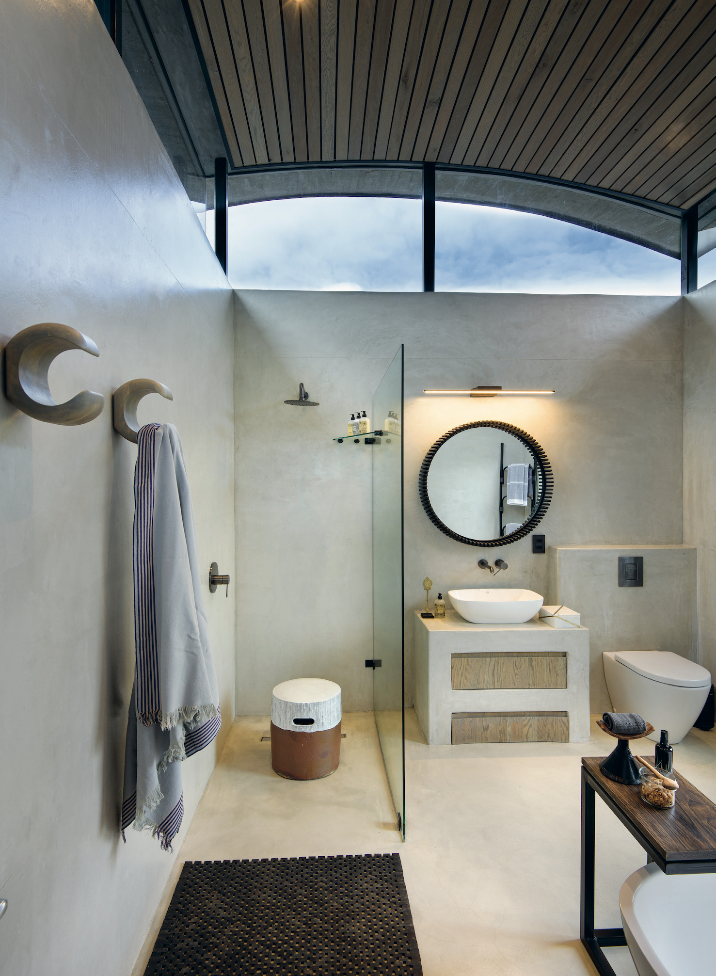 The en-suite bathrooms were designed in neutral tones, with tons of windows to continue the connection to the outdoors. Repeating the cattle theme, the towel hooks are inspired by cow horns.