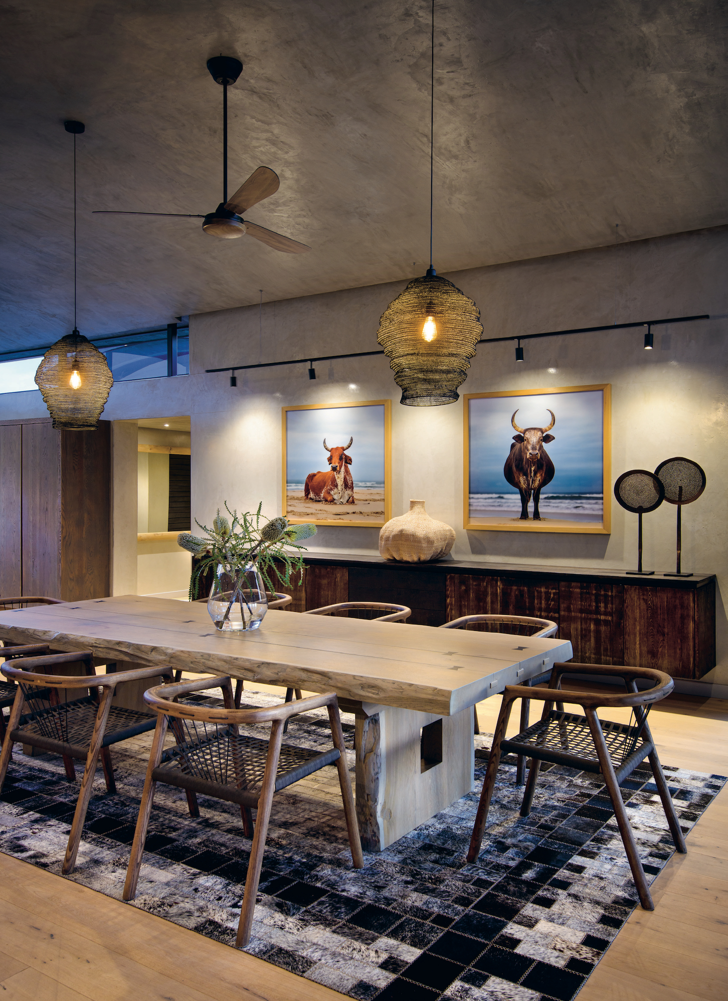 The dining room features a custom-made table. A subtle cattle theme was inspired by papier-mâché finds, and is reflected in the artworks by Daniel Naudé. Patchwork leather carpets are a prominent feature throughout.