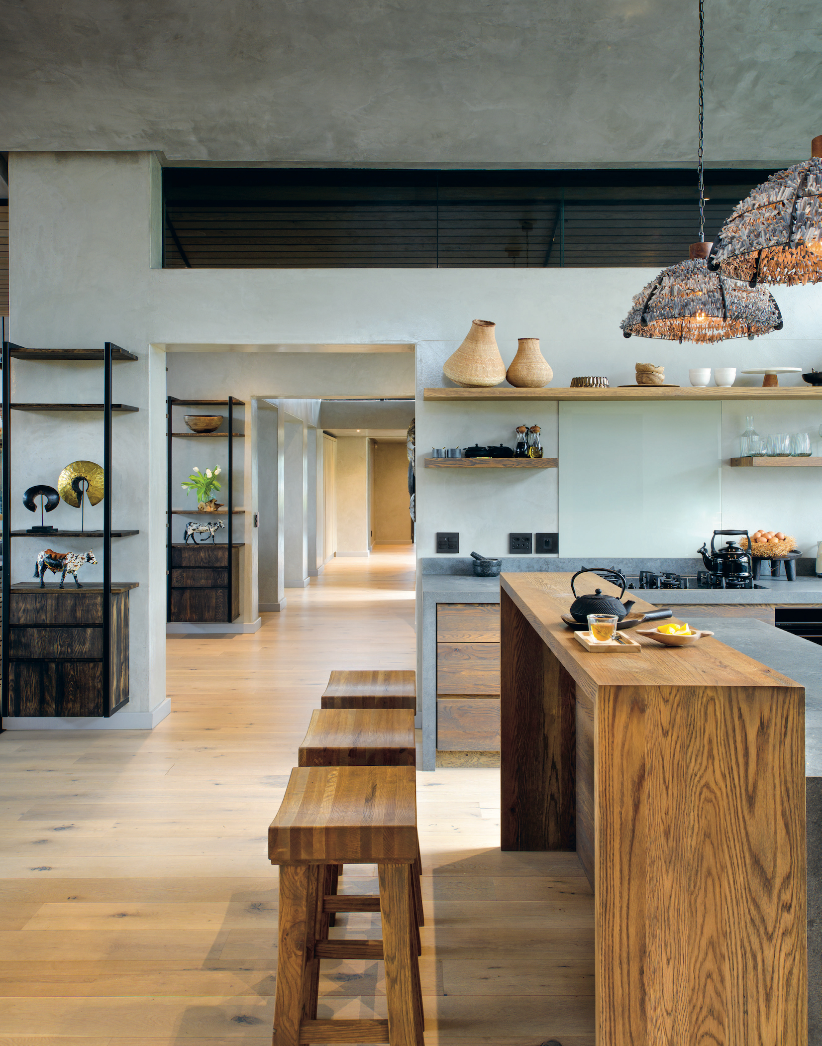 The sleek kitchen features a custom-made breakfast bar. The passageway that links the two wings of the villa runs through the centre of this communal space, and is a showcase of African art.