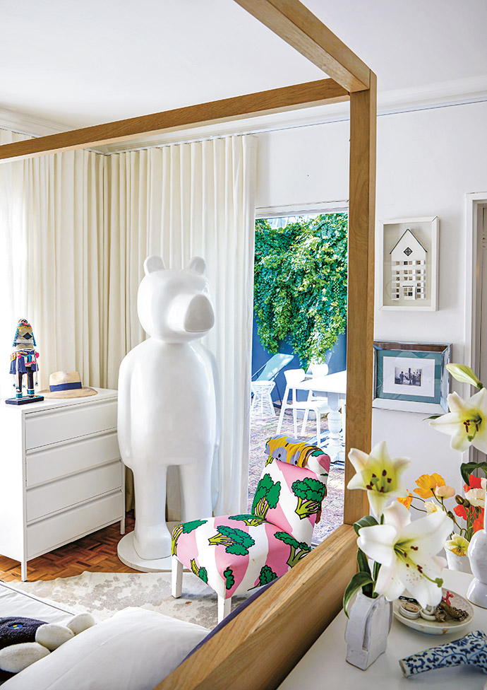In the master bedroom (also shown opposite), Frank's I Am The Bear sculpture stands guard at the door. The four-poster bed is from Weylandts, and the chest of drawers is from Popstrukt Furniture.