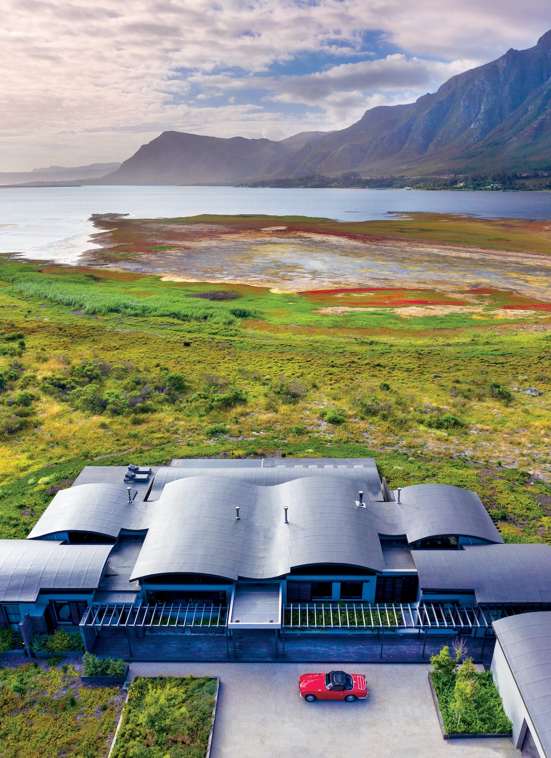 The undulating roof of the Perivoli Lagoon House near Stanford is designed to mirror the local mountain range and blend with its natural surroundings.