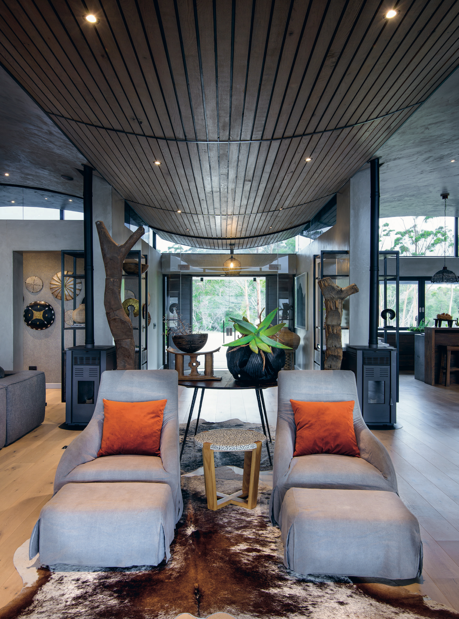 The view from the deck through the villa. The spacious open-plan common area is divided into a lounge and dining space, leading into the kitchen beyond.