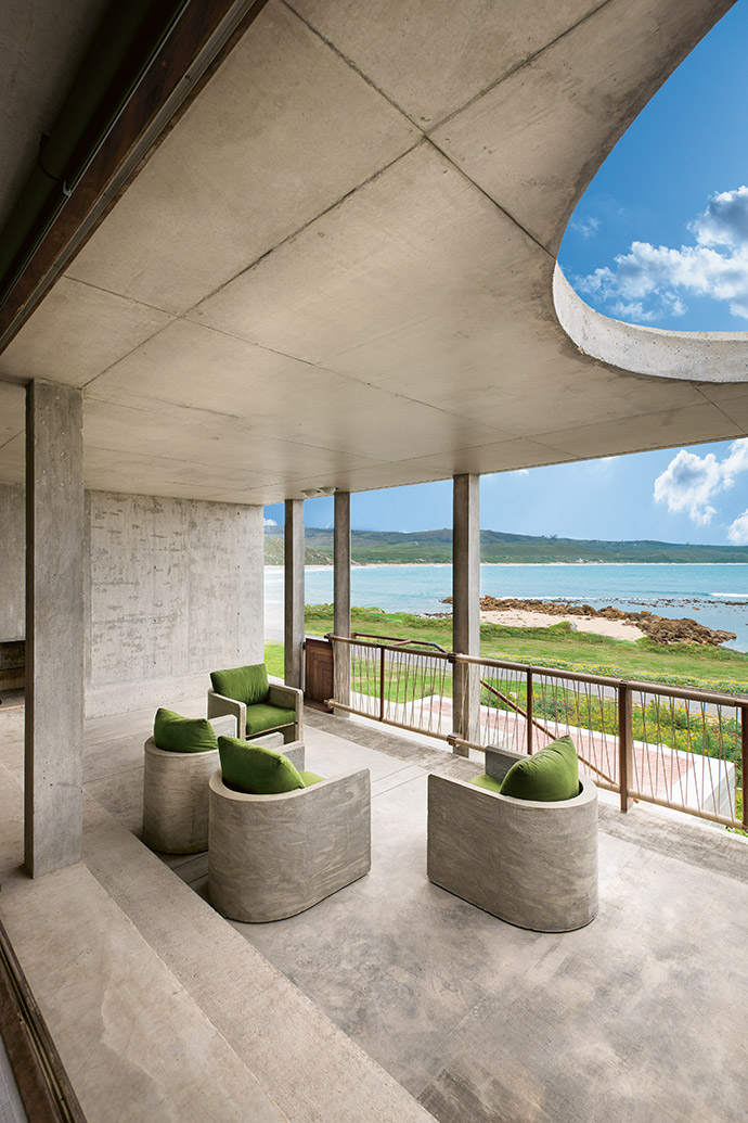 The concrete chairs on the shaded veranda are both cool and functional, providing a vantage point from which to observe the changing moods of the ocean.