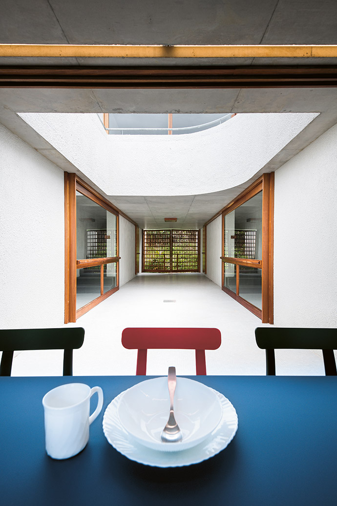 A long table at the entrance of the home functions as a dining space during meal times or the spot for a game of table tennis. Large sliding doors (each with rail handles for wet swimming costumes and damp beach towels) lead to two of the bedrooms.