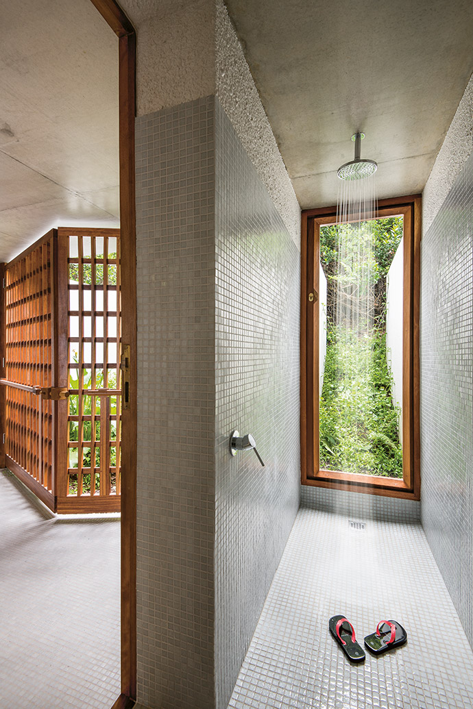 Finished in mosaic tile and rough-textured plaster, the light-filled shower becomes part of the serene milkwood forest outside.
