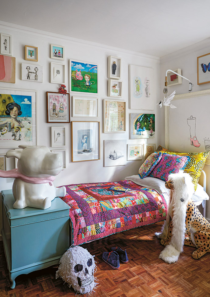 The wall above the bed is filled with Frank's work as well as the work of artist Sarah Pratt.