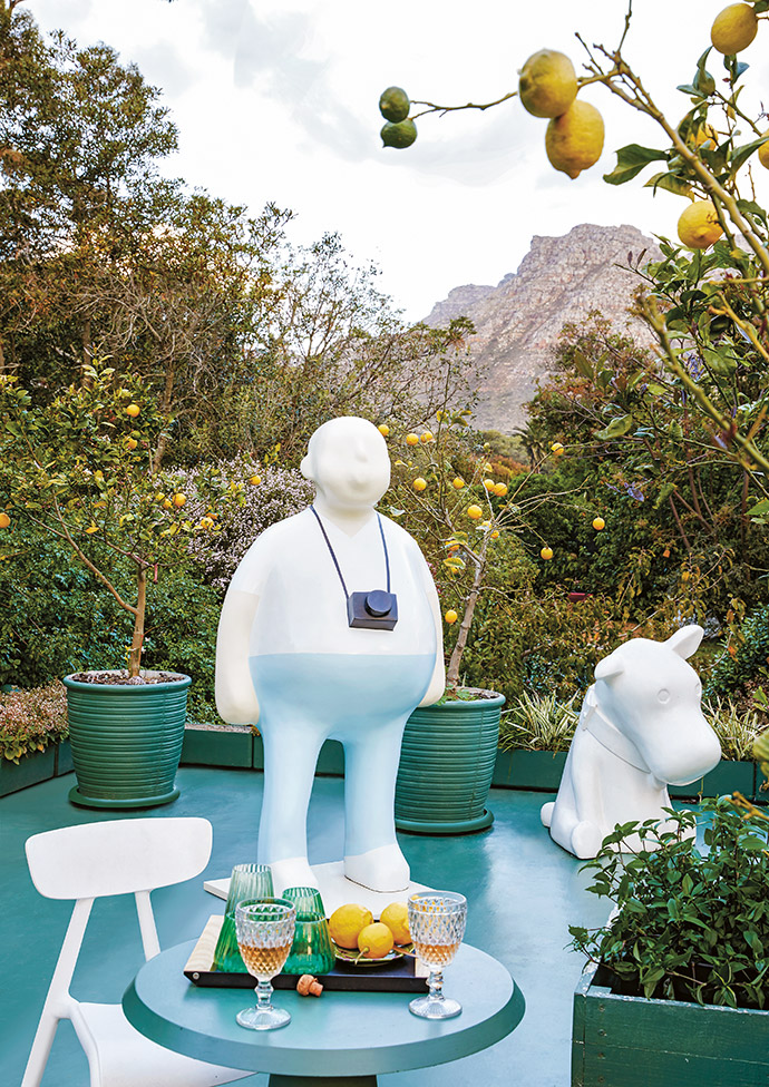 """Tracy's eye for reinvention saw her transform the flat roof of the house into a roof terrace and garden, to better capture the views of the surrounding mountains. Complete with a dining area, a daybed and an """"orchard"""" of lemon trees in pots, the terrace also features Frank's two-metre Tourist sculpture as well as Sitting Dog."""