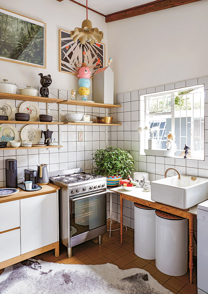 The kitchen is utilitarian, and defined by simple white cabinets and tiles.