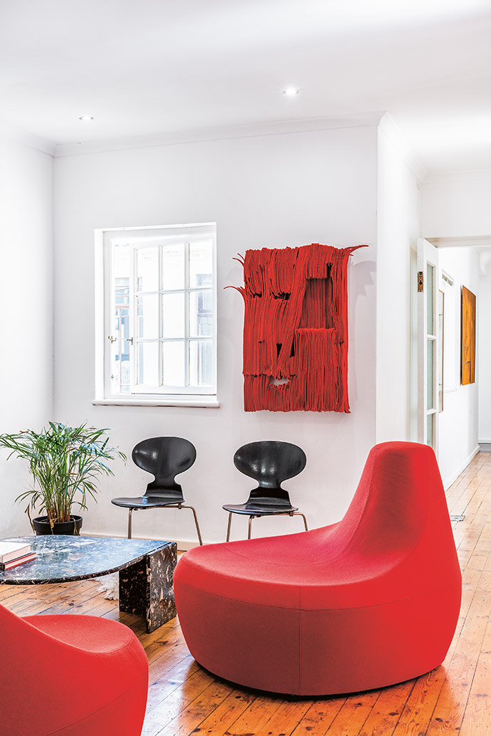 Two red Saruyama settees by Toshiyuki Kita for Moroso (courtesy of True Design) greet guests in the foyer. They are joined by Ant chairs by Arne Jacobsen for Fritz Hansen, and an artwork by Unathi Mkonto.