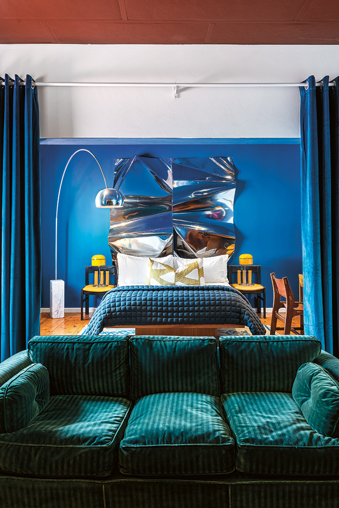 A stainless-steel artwork by homeowner Rodan Kane Hart acts as a decorative headboard in the apartment's master bedroom. The Arco lamp by Achille and Pier Giacomo Castiglioni for Flos is accompanied by vintage finds.