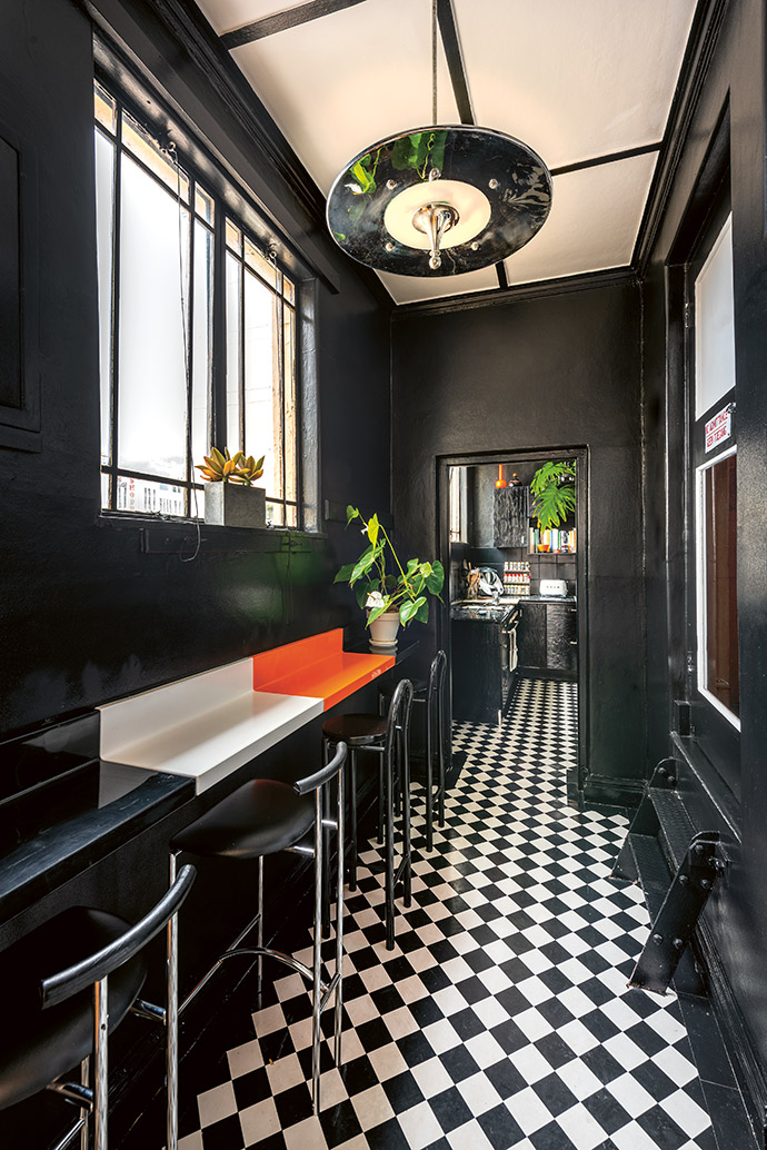 Original chequered linoleum tiles in the kitchen are complemented by Kartell shelves by Achille and Pier Giacomo Castiglioni that have been joined together to form a breakfast counter. The Tokyo stools are by Rodney Kinsman.