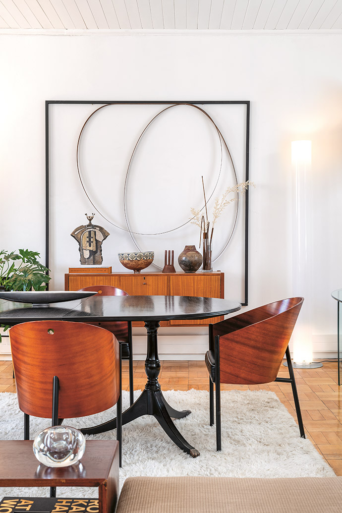 The Stylos floor lamp by Achille Castiglioni for Flos illuminates one of Rodan's wall sculptures as well as vintage objects and ceramics. Costes chairs by Philippe Starck for Driade surround the dining table.