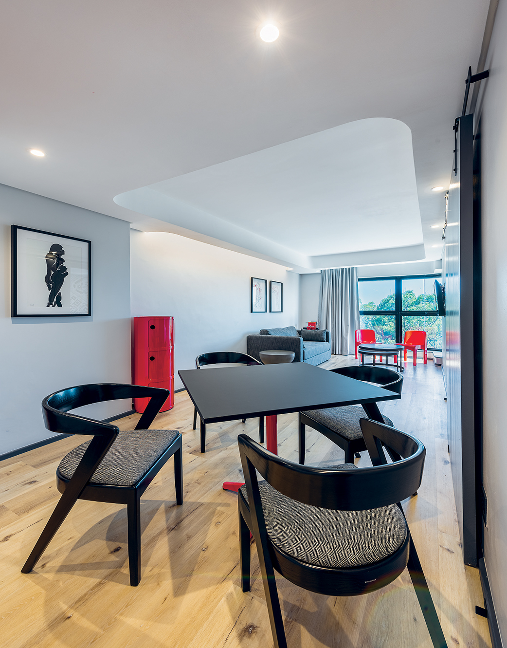 The roomy suite includes a dining area, furnished courtesy of Woodbender and Tabletops, as well as a sleeper couch by Sofaworx, vintage red Kartell stacking chairs sourced from Ride A White Swan, a glossy red storage canister by Chair Crazy, and original artworks by Shafina Jaffer.