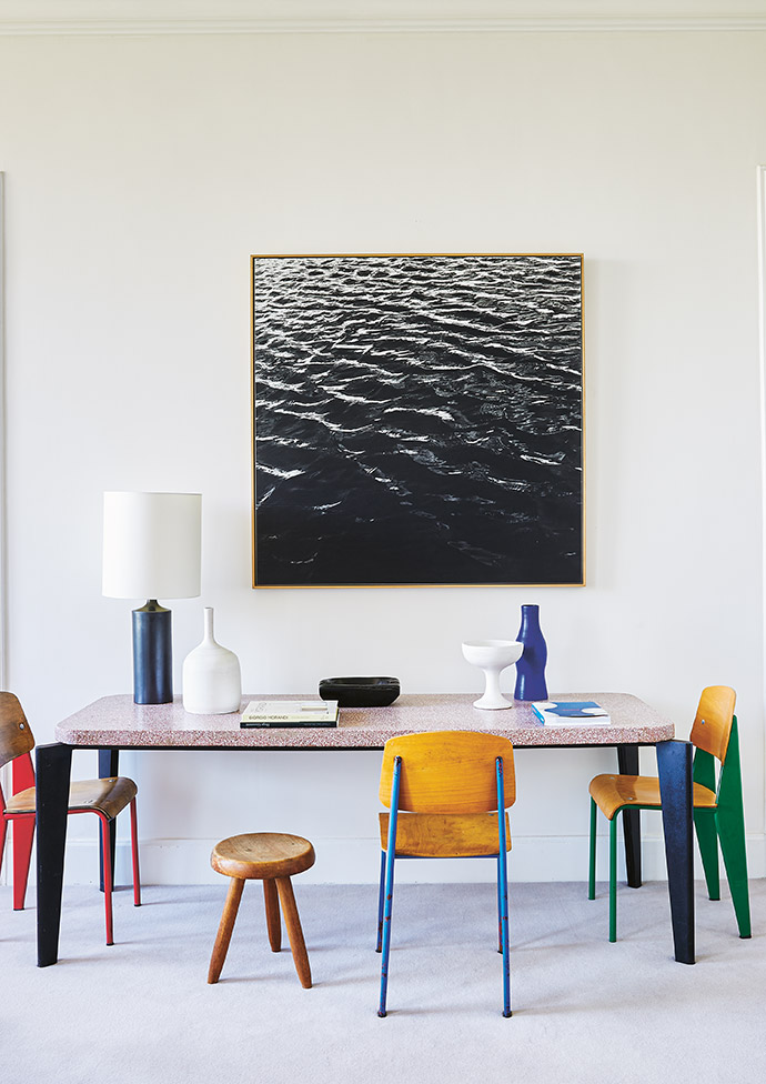 A space for work or dining is tucked away on one side of the living room. The table and Standard chairs are by Jean Prouvé, and the stool is by Charlotte Perriand. The artwork is by German artist Frauke Eigen.