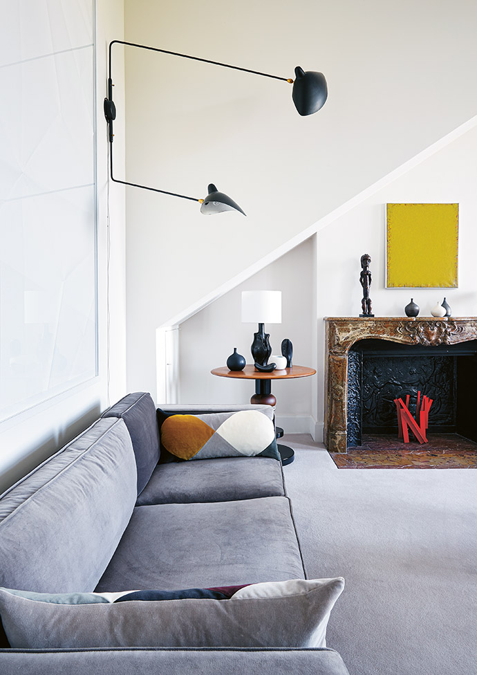 In the living room, tall arched windows flood the space with light. A grey sofa and round wooden Starr table by India Mahdavi complement both the original fireplace and the wall-mounted mid-century modern light fitting by Serge Mouille. The lounge suite and wooden shelving unit are by Pierre Jeanneret, the coffee table is by industrial designer Ron Arad, and the colourful ceramics are by Georges Jouve.
