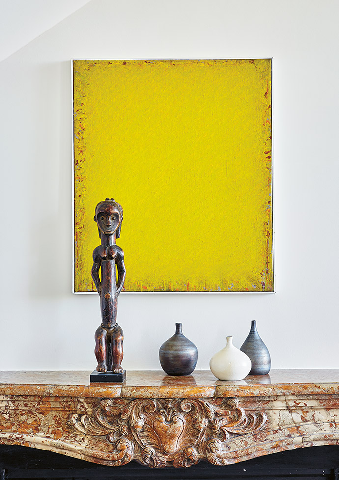 An artwork by German artist Bernd Berner forms the backdrop for Georges Jouve ceramics and an African figurine.