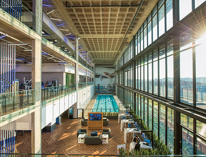 Planet Fitness Olympus features a rooftop running track and floor-to-ceiling glazed windows to connect the industrial, concrete-and-steel interior to the great outdoors.