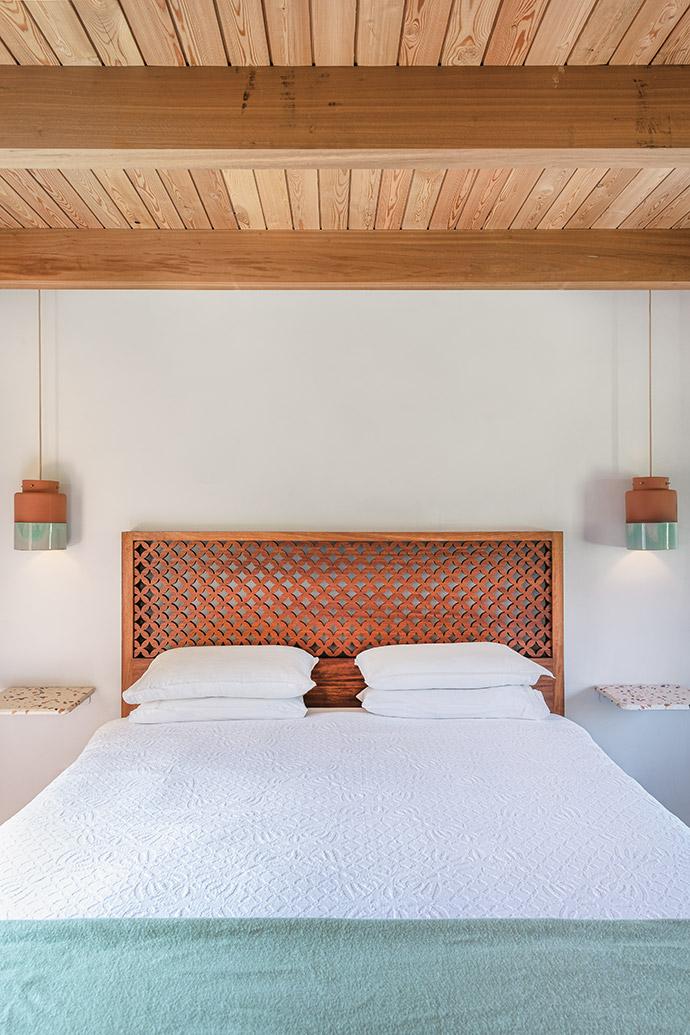In the bedroom, a headboard sourced at Saba Studios in Lamu, Kenya lives alongside ceramic pendants from Wiid Design.