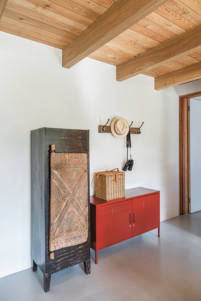 An industrial locker from Popstrukt offsets the wooden bookcase leftby the previous owner. The hooks are repurposed from Private Collections door frames.