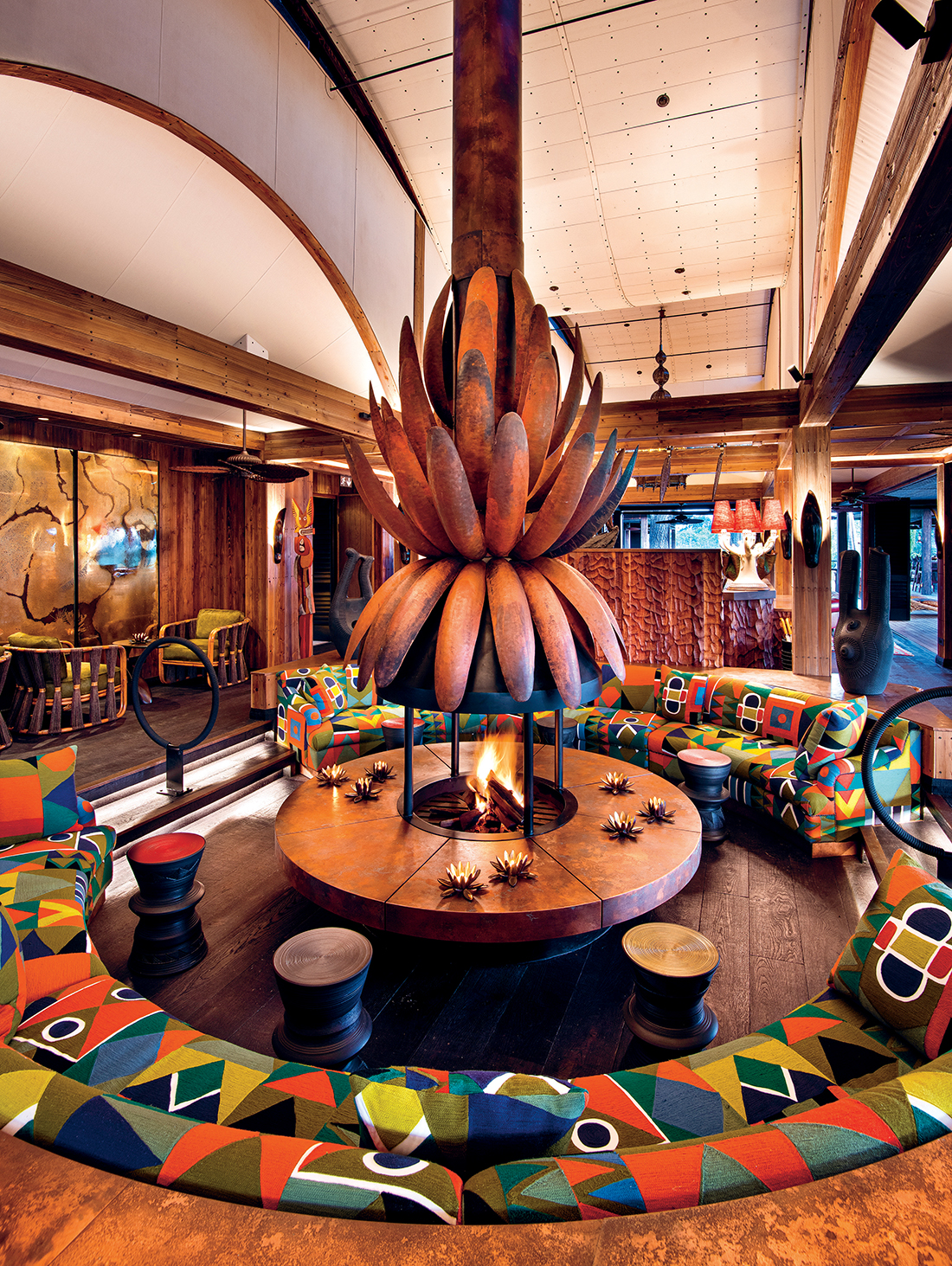 On arrival at Xigera, one of the first spaces guests see is this sunken lounge. The chimney piece is an interpretation of the water lily – the lodge's emblem – by Otto du Plessis and Charles Haupt of Bronze Age. The built-in couches are upholstered in Pierre Frey Ndebeles fabric in Argile, and the ceramic Imbizo side tables are by Chuma Maweni.
