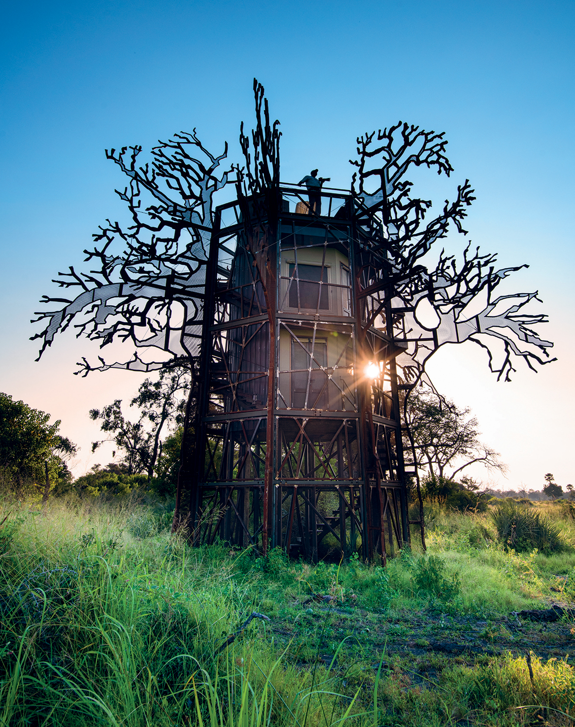 """Rising 10 metres above the floodplain, Xigera's three-storey baobab """"treehouse"""" – also designed by architect Anton de Kock – offers 360-degree views and has steel branches already rusting into visual harmony with the surrounding bush. Guests can choose to spend a night here, sleeping under the stars in an open-air bed"""