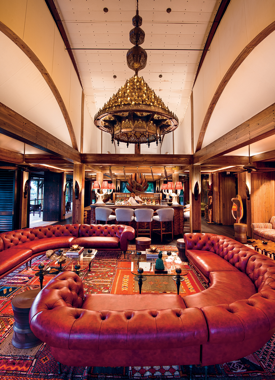 """Xigera is """"a celebration of life and art and colour"""", says Toni. In this lounge area in the main lodge, curved leather sofas invite guests to linger. The Moroccan chandelier – by maven of Marrakech design Bill Willis – and rug add North African glamour."""