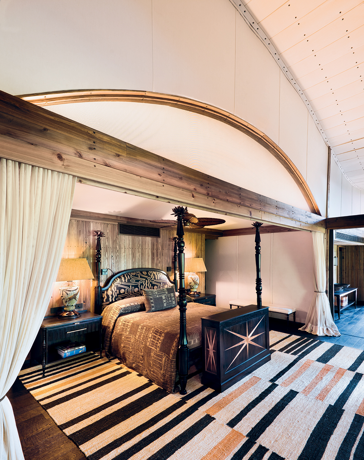 The four-poster bed in this suite is topped with cast-bronze water-lily finials, and the headboard is upholstered in Tasmania fabric in Ebène by Pierre Frey. The bedside lamps are by Ardmore Design, and the rug was made by Coral & Hive.