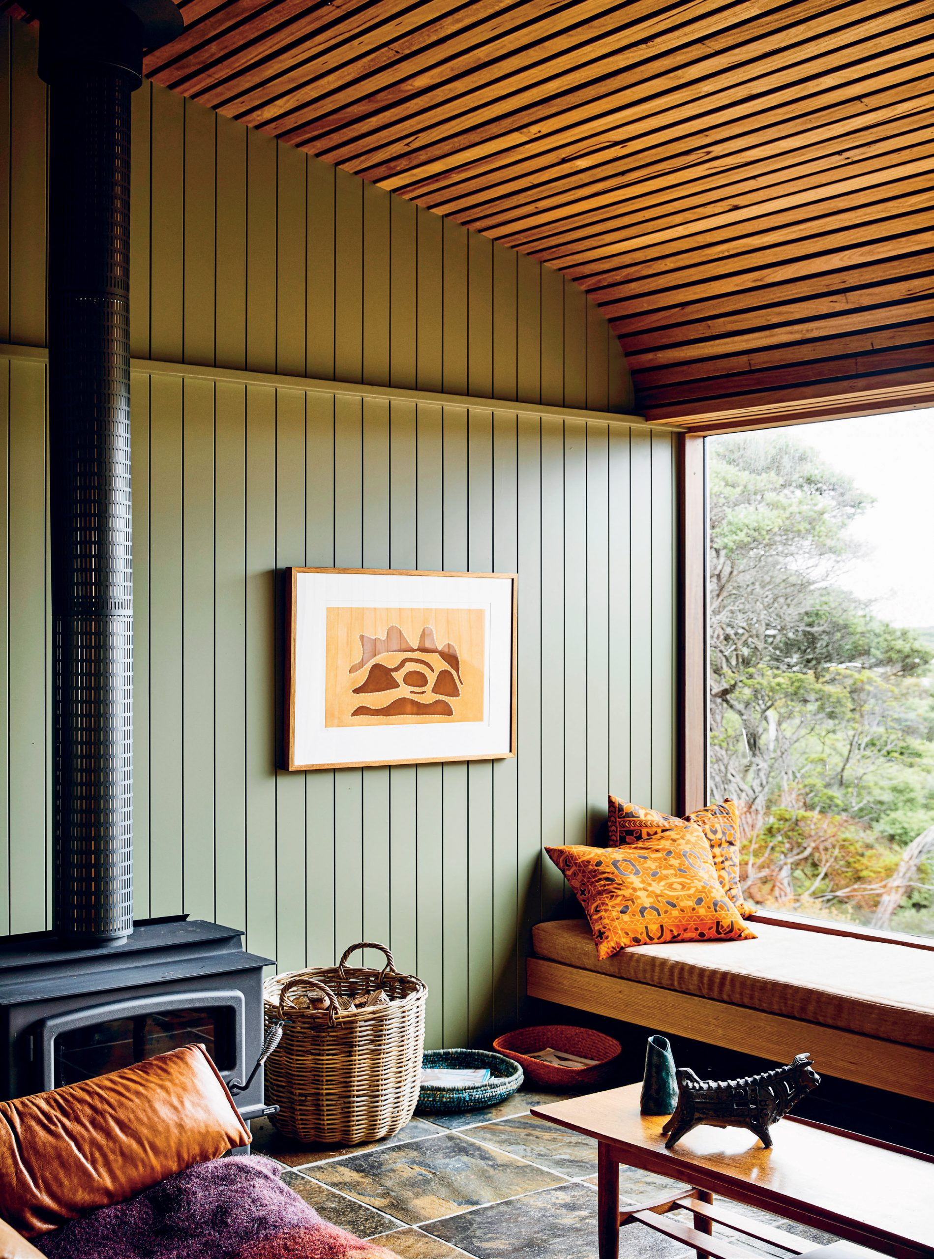 In the living area, an artwork by indigenous artist Shirley Purdie hangs next to the Nectre slow-combustion wood heater.