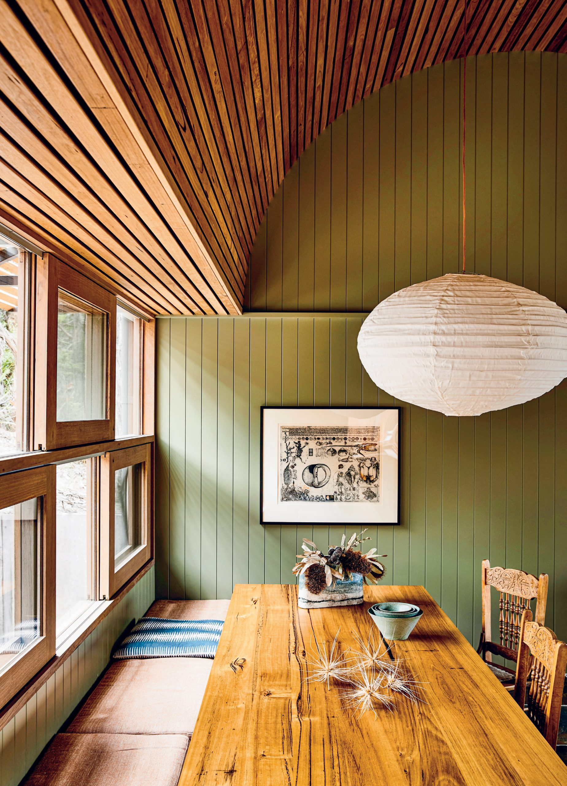 The space has been designed to fit multiple generations, and the large Mark Tuckey dining table provides ample seating for whoever is staying. An artwork by Jörg Schmeisser creates visual contrast against the green.