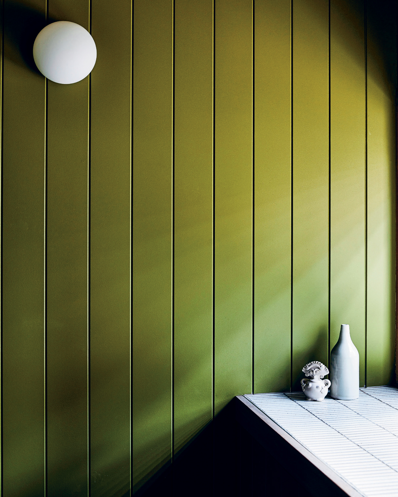 """Walls painted in Dulux """"Spores"""" tie in with the home's bushland surrounds, and provide a neutral backdrop for the rounded light fittings and white ceramics."""